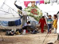 شاهد صورة طفل عراقي نازح يؤدي واجباته الدراسية أمام الخيمة التي تأويه مع عائلته