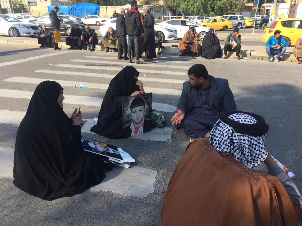 بالصور  ..  العشرات من ذوي شهداء سبايكر يقطعون شارع كرادة مريم المقابل لمبنى البرلمان لعدم تسليم جثث ابنائهم