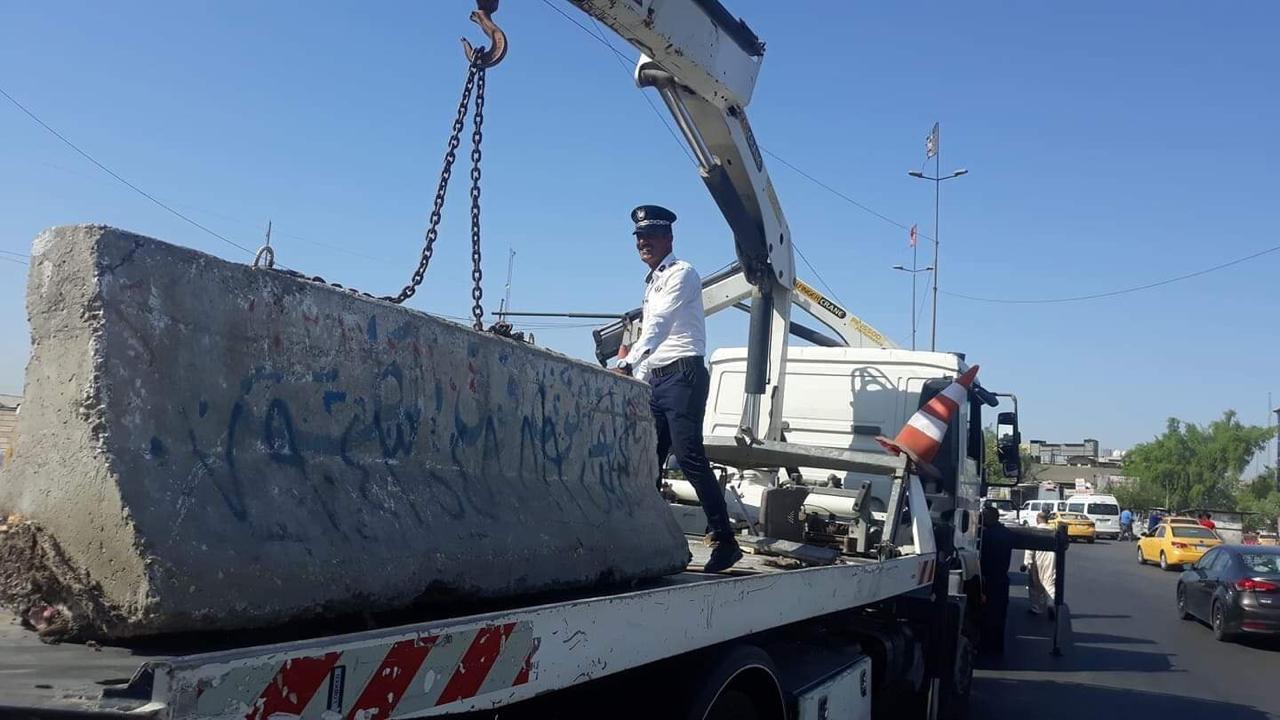 بالصور ..  رفع الكتل الكونكريتية من مدخل منطقة بغداد الجديدة